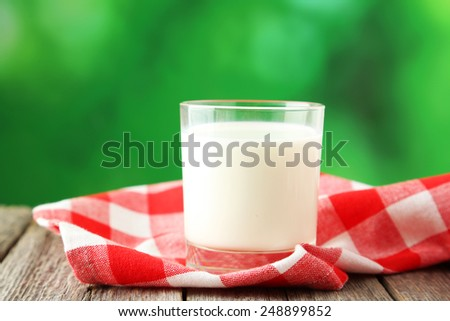 Glass of milk on grey wooden background - stock photo