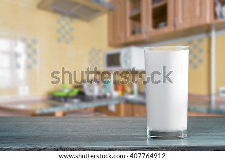 Glass of milk on the kitchen table - stock photo