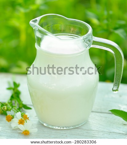 Glass of milk  on white  table  in morning garden - stock photo