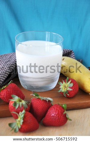 Glass of milk with fresh banana and strawberries