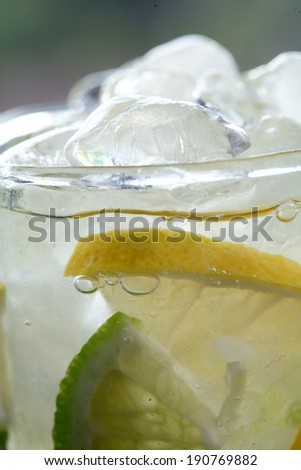 Glass of mineral water with ice cubes and lemon/ lime  slice