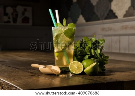 Glass of Mojito cocktail on a wooden table with brown caster sugar, lime, mint sprigs, copy space  - stock photo
