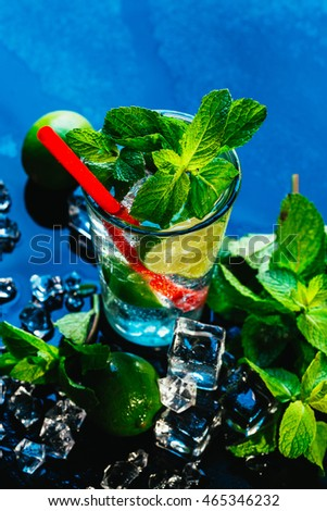 glass of mojito with lime and mint ice cube close-up with red straw on blue background.
