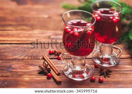Glass of mulled wine with cranberry and scented cinnamon sticks on a wooden table - stock photo