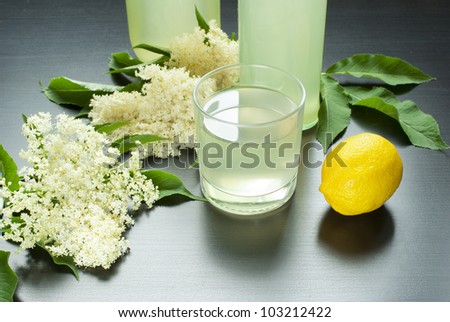 glass of natural elderflower juice with lemon and elder-flowers