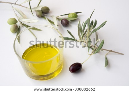 glass of olive oil with raw olives