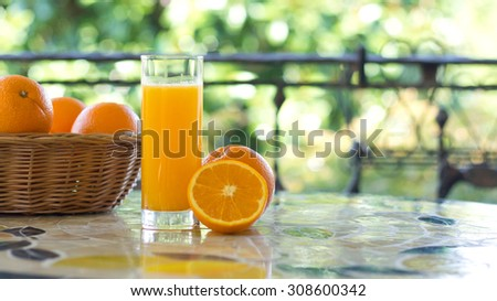 Glass of orange juice and fresh oranges on a mosaic table in a terrace - stock photo