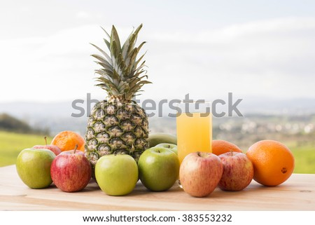 glass of orange juice and lots of fruits on wooden table outdoor - stock photo