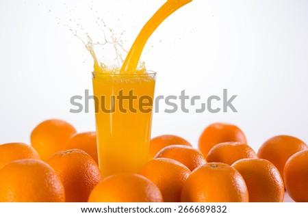 Glass of orange juice creating splash - stock photo