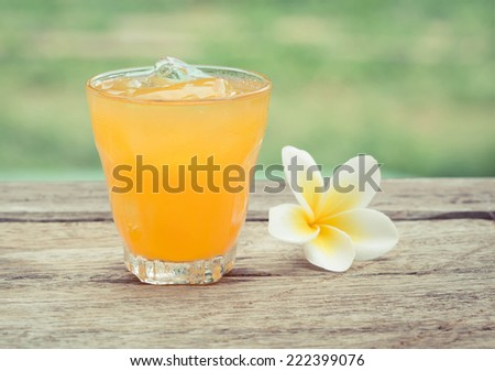 glass of orange juice with ice cubes on wood - stock photo