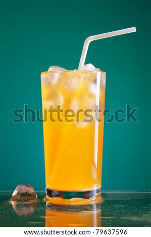glass of orange soda with ice and straw over blue background - stock photo