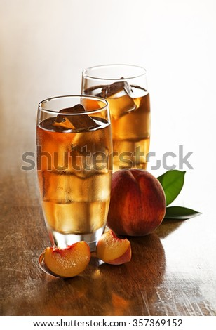 Glass of peach ice tea with slices cubes. - stock photo