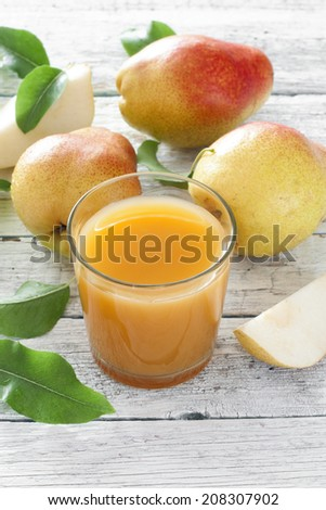 Glass of pear juice and ripe pears over white wood table - stock photo
