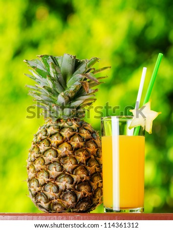 Glass of pineapple juice in a garden. - stock photo