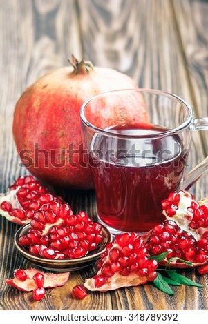 glass of pomegranate juice with ripe fresh punica granatum fruits with leaves on wooden table close-up - stock photo