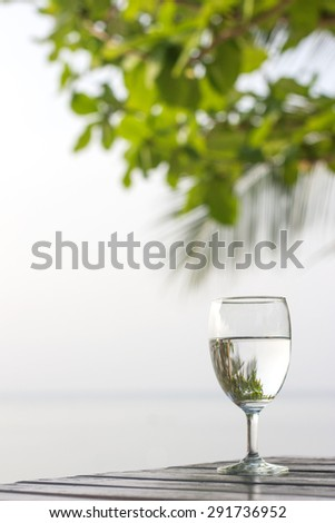 Glass of pure water on a dark table on the beach with a palm tree in the background. - stock photo