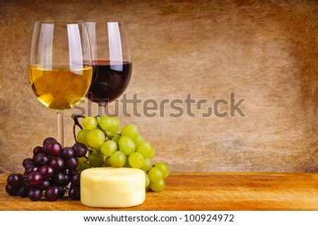 glass of red and white wine, cheese and grapes on a wooden background - stock photo