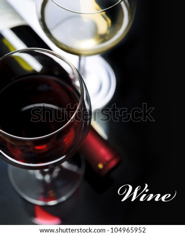 Glass of red and white wine on black background - stock photo