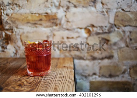 Glass of red cocktail or juice cocktail on the wooden table and brick background. - stock photo