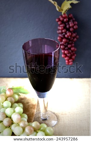 glass of red grape juice with grapes on background - stock photo