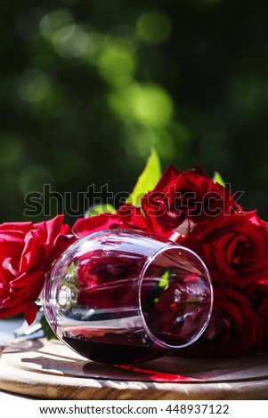 Glass of red wine and a bouquet of red roses, natural background, selective focus