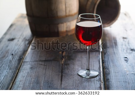 Glass of red wine and a old barrels at the wood table - stock photo
