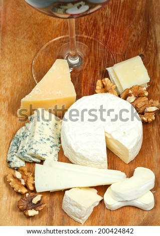 glass of red wine and assorted cheeses on wooden plate close up - stock photo