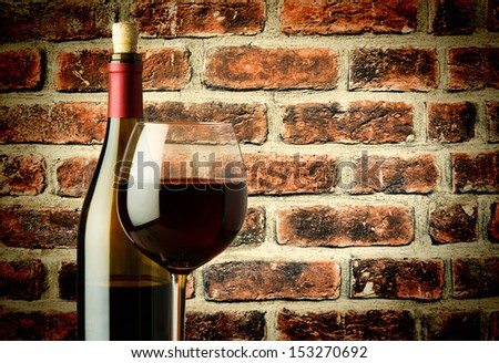 glass of red wine and bottle in a wine cellar near the brick wall - stock photo