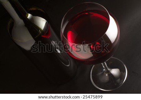 Glass of red wine and bottle on black background. - stock photo