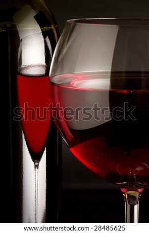 Glass of red wine and bottle on black background.