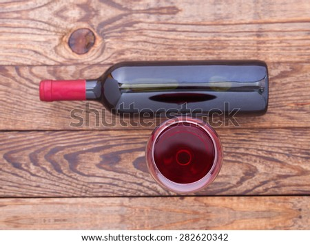 Glass of red wine and bottle on wooden background. Flat mock up for design. - stock photo
