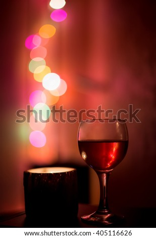 Glass of red wine and candle on a background
