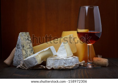 Glass of red wine and cheese assortment on wooden table still life - stock photo