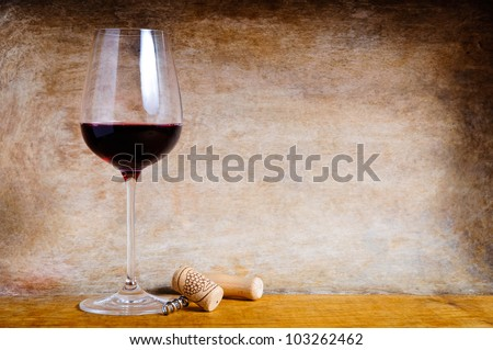 Glass of red wine and cork screw on a wooden background with text copy space - stock photo