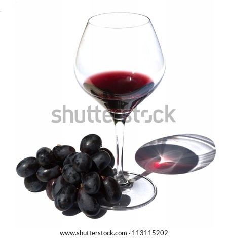 Glass of red wine and grapes in sunlight