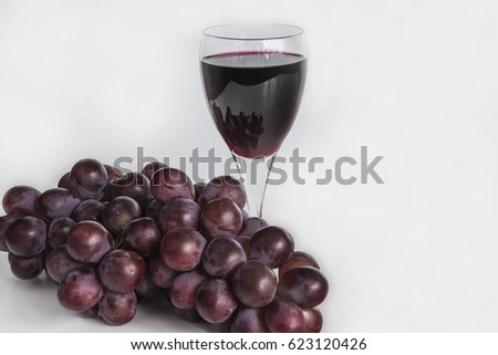 glass of red wine and red grapes on white background