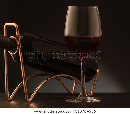 Glass of red wine and red wine bottle  on a metal wine rack - stock photo