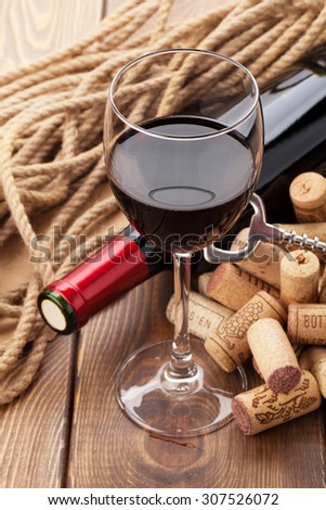Glass of red wine, bottle and corks on rustic wooden table - stock photo