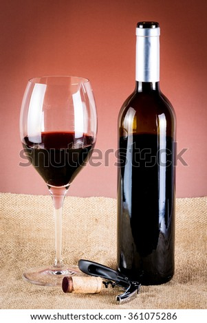 glass of red wine, bottle of wine, corkscrew - stock photo