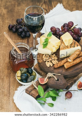 Glass of red wine, cheese board, grapes,fig, strawberries, honey and bread sticks  on rustic wooden table, selective focus - stock photo