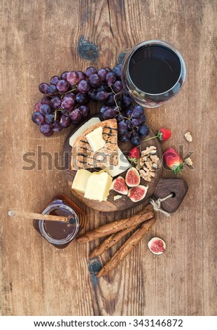 Glass of red wine, cheese board, grapes,fig, strawberries, honey and bread sticks  on rustic wooden table, top view - stock photo