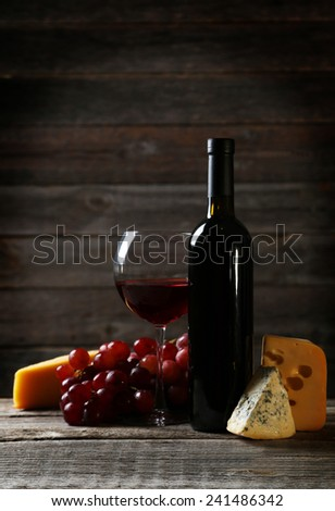 Glass of red wine, cheeses and grapes on grey wooden background