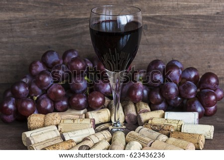 glass of red wine,corks and grapes on wooden background