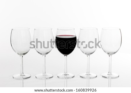 Glass of red wine in a row of empty glasses, on white background.