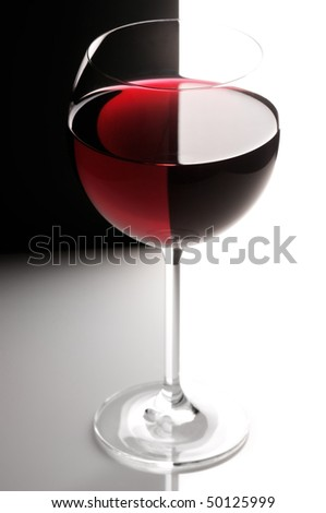 Glass of red wine in back light on black&white background. - stock photo