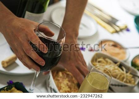 Glass of red wine in woman's hand at business lunch or buffet, dynamic close up on red wine glass. - stock photo
