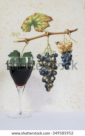 glass of red wine on a decorative background, romantic moment in Italy, background decorated with a drawing of a cluster of grapes, natural light, vertical photo, front view - stock photo