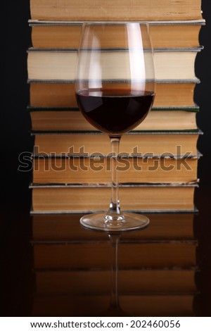 Glass of red wine on a reflective surface with books