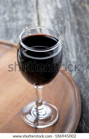 glass of red wine on a wooden board, top view - stock photo
