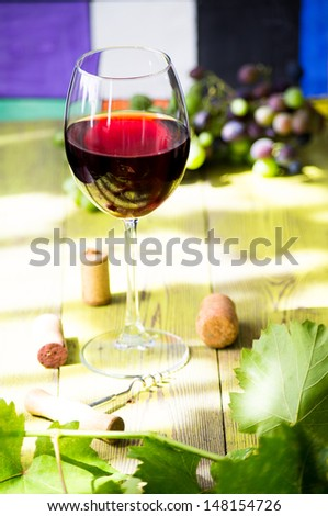 Glass of red wine on a wooden table with leaves of grapes, corkscrew and wine corks and a bunch of young grapes.